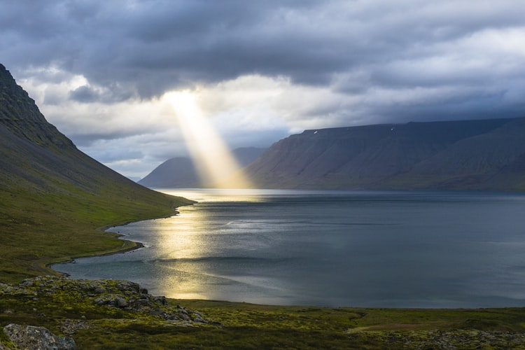 Pic: Light coming out of the sky on a beach surrounded by mountains. Does God Exist?