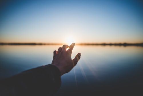 Pic: A hand towards the sunlight. Is God real?